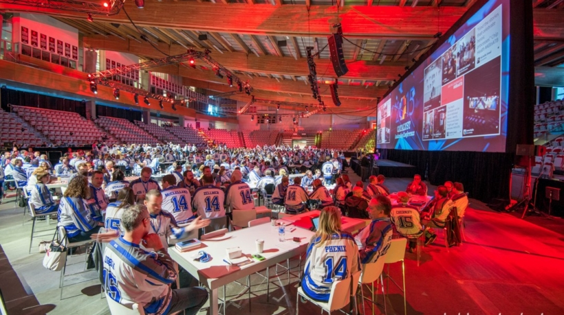 Wide angle event photography of guests listening to the keynote speaker on stage